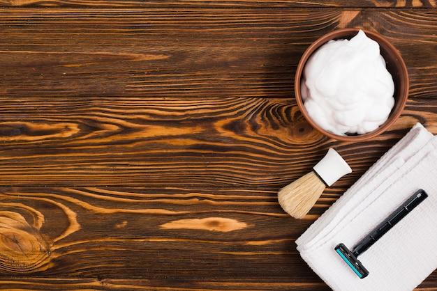 Una vista dall'alto della ciotola di schiuma; pennello da barba; rasoio e tovagliolo piegato bianco contro il contesto strutturato di legno Foto Gratuite