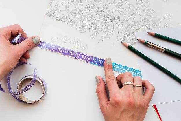 Una vista dall'alto della mano della donna che attacca il pizzo su carta da disegno Foto Gratuite