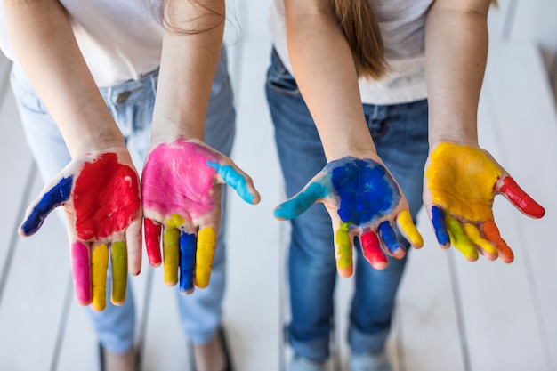 Una vista dall'alto della mano di due ragazze che mostrano le loro mani dipinte Foto Gratuite