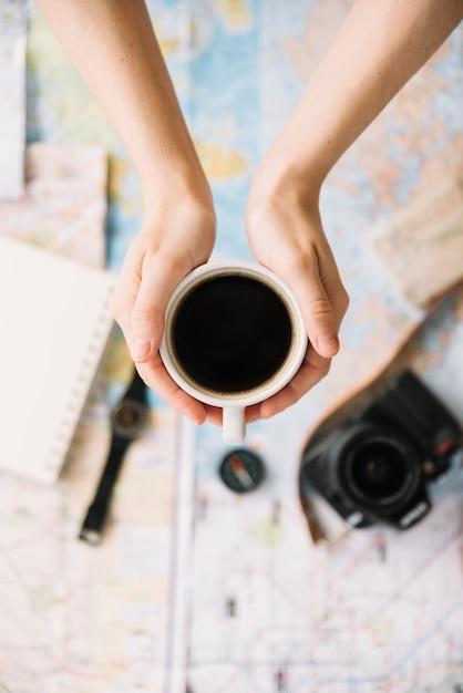 Una vista dall'alto della mano di una persona che tiene tazza di caffè sulla mappa sfocata Foto Gratuite