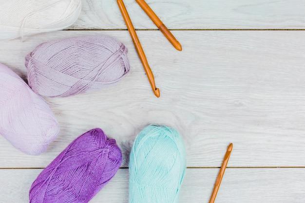Una vista dall'alto della palla di filato colorato e aghi a maglia sul tavolo di legno Foto Gratuite