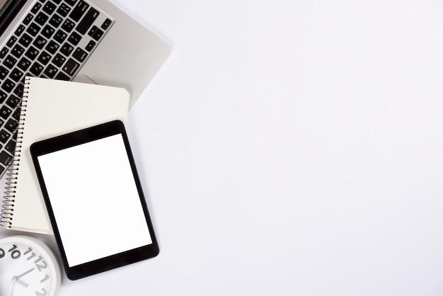 Una vista dall'alto della tavoletta digitale; blocchetto per appunti sul computer portatile con la sveglia isolata su priorità bassa bianca Foto Gratuite