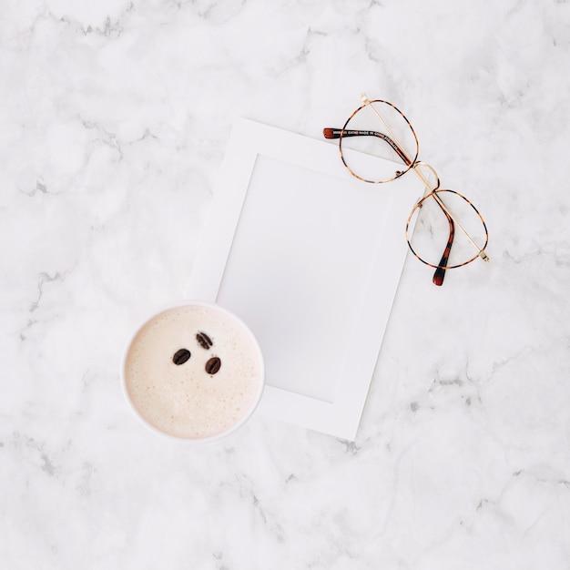 Una vista dall'alto della tazza di caffè usa e getta; cornice vuota e occhiali da vista su marmo con texture di sfondo Foto Gratuite