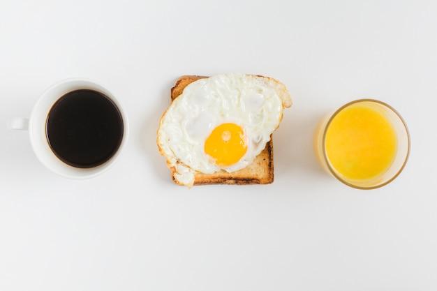 Una vista dall'alto della tazza di tè; bicchiere di succo e pane tostato con uovo fritto isolato su sfondo bianco Foto Gratuite