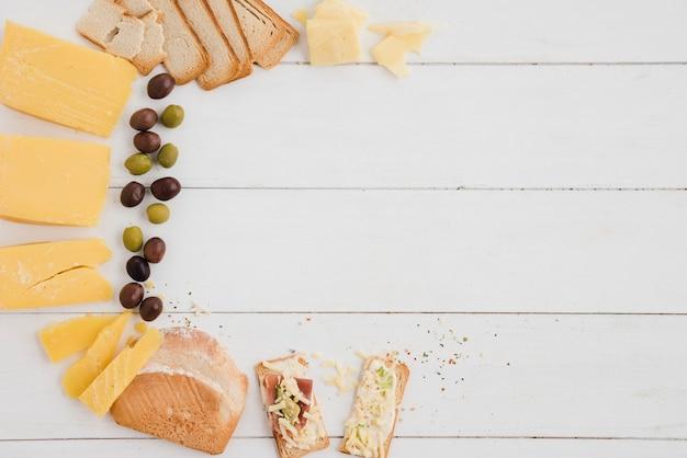 Una vista dall'alto delle olive; fetta di formaggio e pane sul tavolo di legno bianco Foto Gratuite