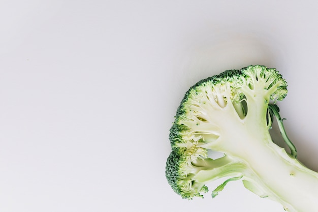 Una vista dall'alto di broccoli divisi a metà sull'angolo dello sfondo bianco Foto Gratuite