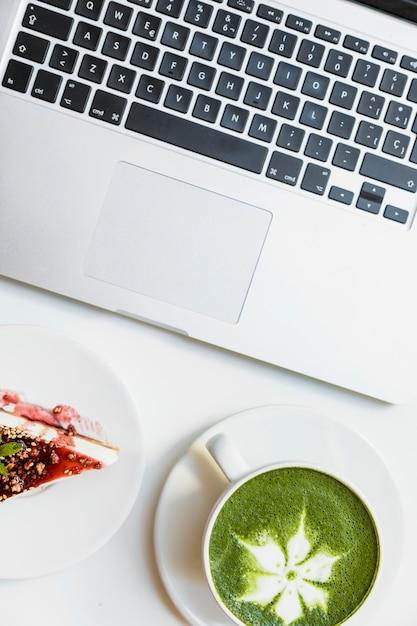 Una vista dall'alto di cheesecake ai frutti di bosco; matcha del tè verde e computer portatile sullo scrittorio bianco Foto Gratuite