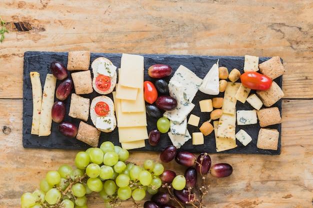 Una vista dall'alto di formaggio, uva e mini pane a bordo di ardesia sopra il tavolo Foto Gratuite