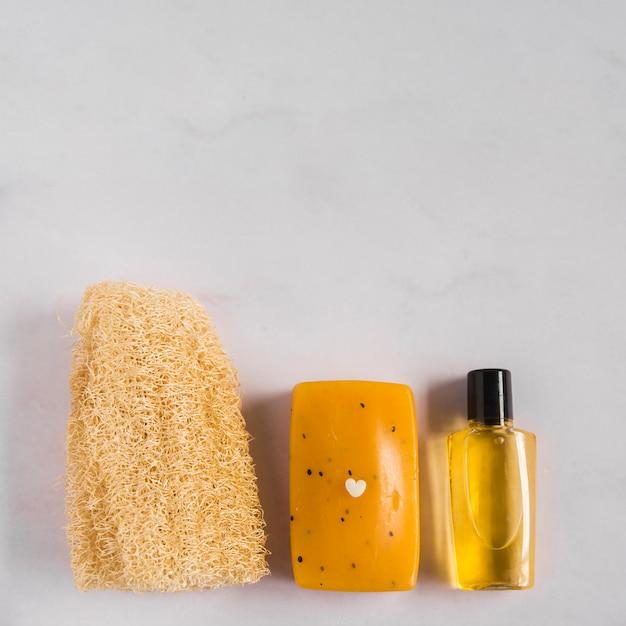 Una vista dall'alto di luffa naturale; sapone a base di erbe e bottiglia di olio essenziale su sfondo bianco Foto Gratuite