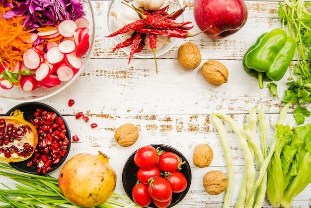 Una vista dall'alto di pomodorini; peperoncini rossi; cipollotto; aglio; lattuga; prezzemolo; melograno maturo; rossastro e noce Foto Gratuite