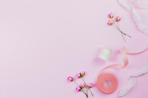 Una vista dall'alto di rose artificiali; bobina e nastri su sfondo rosa Foto Gratuite