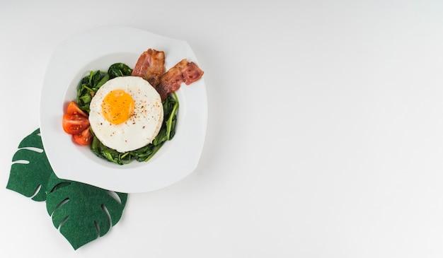 Una vista dall'alto di un uovo fritto con spinaci; pomodoro e pancetta sul piatto bianco su sfondo bianco Foto Gratuite