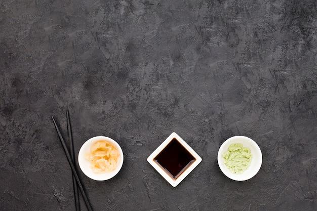 Una vista dall'alto di zenzero marinato; wasabi e salsa di soia con bacchette sulla lavagna Foto Gratuite