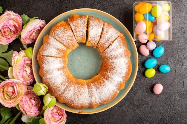 Una vista dall'alto dolce torta rotonda con zucchero in polvere insieme a caramelle colorate a fette dolce delizioso dolce isolato all'interno della piastra e sfondo grigio biscotto zucchero biscotto Foto Gratuite