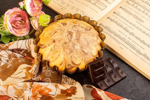 Una vista dall'alto dolce torta rotonda squisita deliziosa all'interno della tortiera insieme a fiori di cioccolato e quaderno di note musicali sullo sfondo grigio biscotto di zucchero biscotto Foto Gratuite
