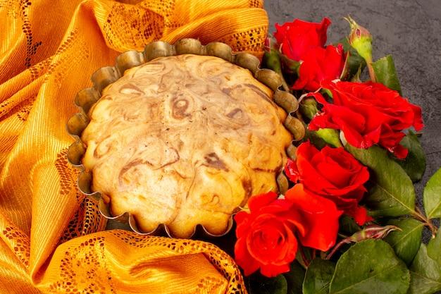 Una vista dall'alto rotonda torta dolce deliziosa e squisita torta al cioccolato all'interno della tortiera insieme a rose rosse isolate su sfondo grigio Foto Gratuite