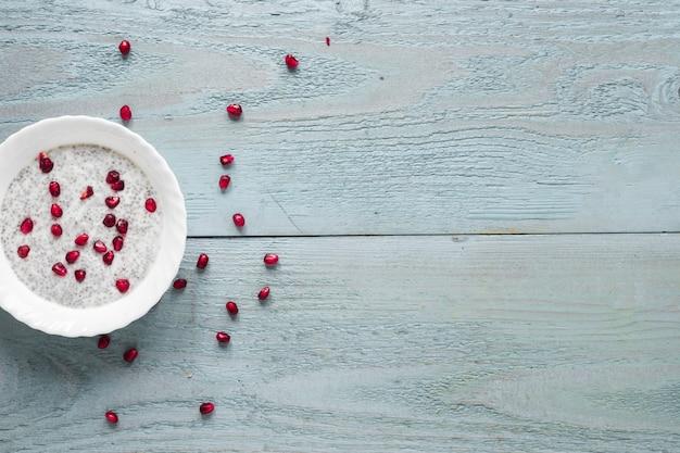 Una vista elevata del budino del seme di chia in ciotola bianca sulla tavola di legno Foto Gratuite