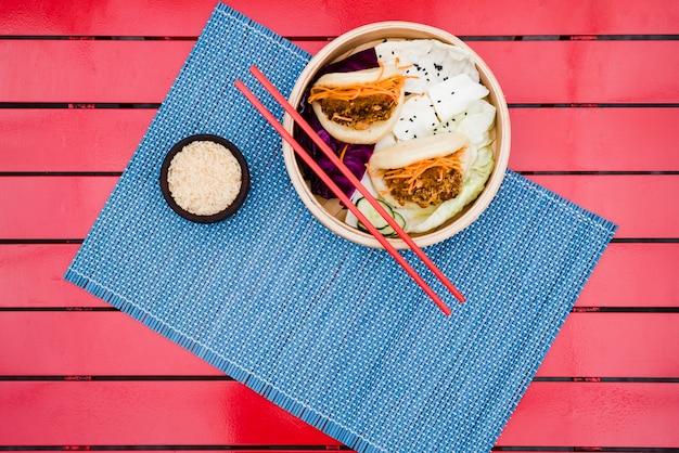 Una vista elevata del pane al vapore piano su placemat blu sopra la tabella rossa Foto Gratuite