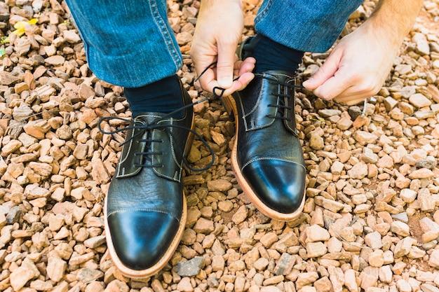 Una vista elevata del piede dell'uomo sul ciottolo che lega i lacci delle scarpe Foto Gratuite