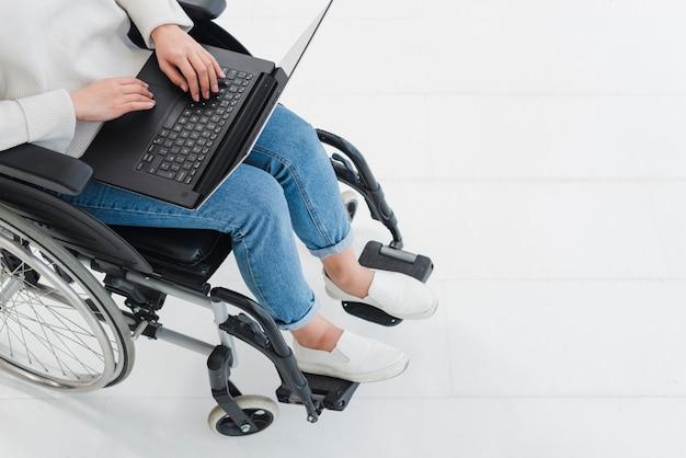Una vista elevata della donna che utilizza computer portatile sulla sedia a rotelle Foto Gratuite
