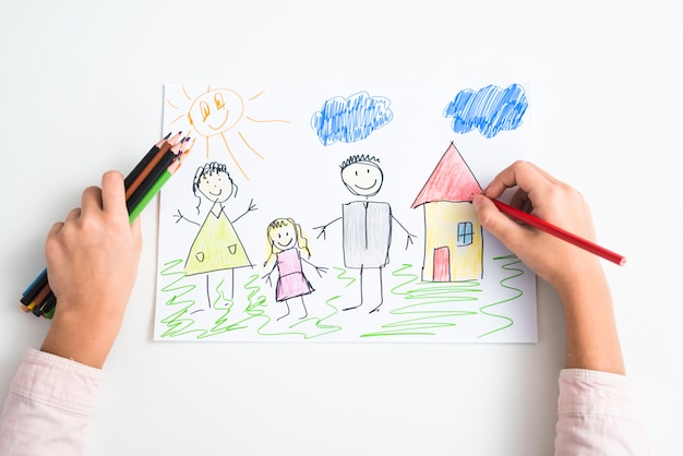 Una vista elevata della mano di una ragazza che disegna la famiglia e la casa con la matita colorata su carta da disegno Foto Gratuite