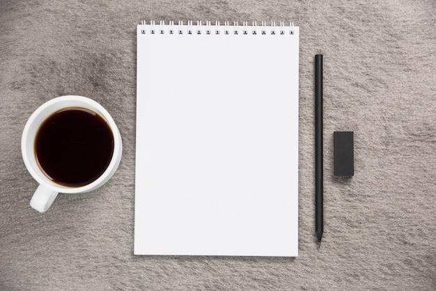Una vista elevata della tazza di caffè; blocchetto per appunti a spirale in bianco con gomma nera e matita su scrivania grigia Foto Gratuite