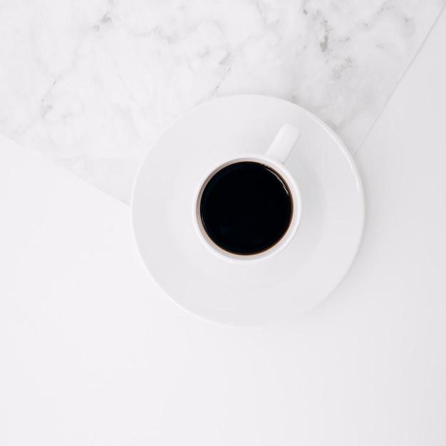 Una vista elevata della tazza di caffè nero sul piattino sullo sfondo di marmo e bianco Foto Gratuite