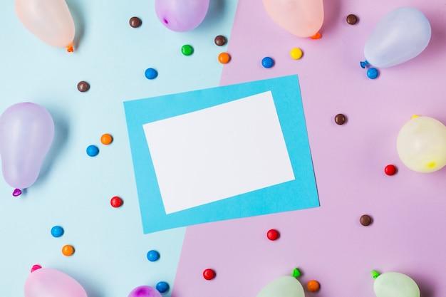 Una vista elevata di carta bianca e blu circondata da gemme e palloncini su sfondo blu e rosa Foto Gratuite