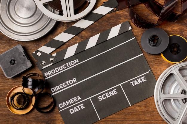 Una vista elevata di ciak; bobine di film; strisce di pellicola su fondali in legno Foto Gratuite