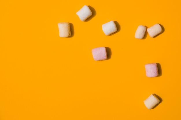 Una vista elevata di marshmallow su uno sfondo arancione Foto Gratuite