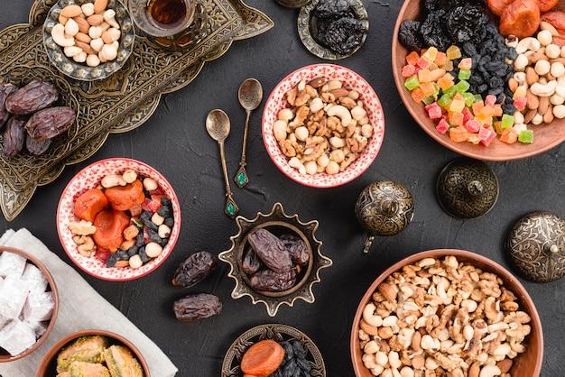 Una vista elevata di noci; date; dolce dessert sulla ciotola in ceramica e metallica sul tavolo di cemento nero Foto Gratuite
