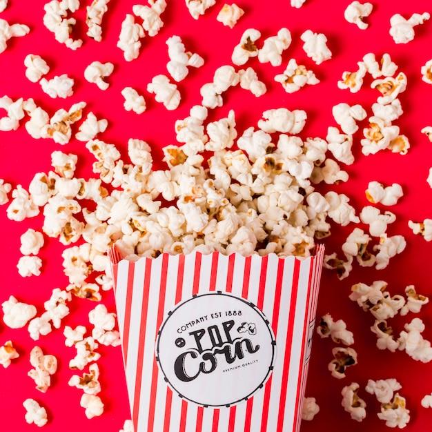 Una vista elevata di popcorn fuoriusciva dalla scatola a strisce sullo sfondo rosso Foto Gratuite