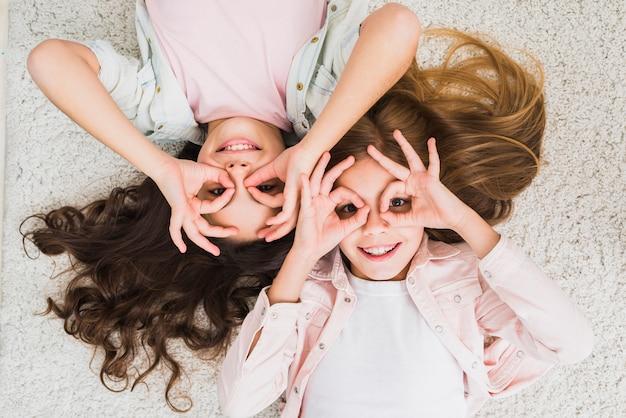Una vista elevata di un amico di due donne che si trova sul tappeto che fa gesto giusto come binoculare che osserva in su Foto Gratuite