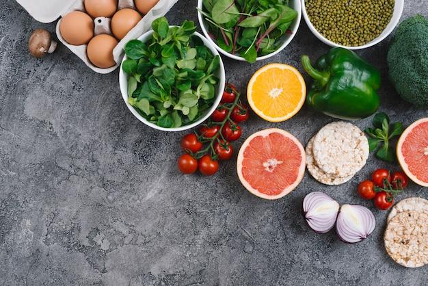Una vista elevata di verdure; uova; agrumi e torta di riso soffiato su sfondo grigio cemento Foto Gratuite