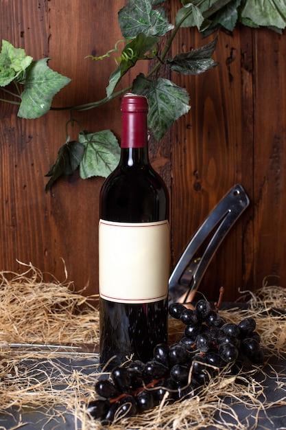 Una vista frontale bottiglia di alcool bottiglia nera con tappo bordeaux con uva nera e foglie verdi su sfondo marrone bere alcolici in cantina Foto Gratuite