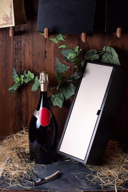 Una vista frontale bottiglia di alcool bottiglia nera con tappo dorato insieme a scatola nera e foglie verdi su sfondo marrone bere alcolici cantina Foto Gratuite