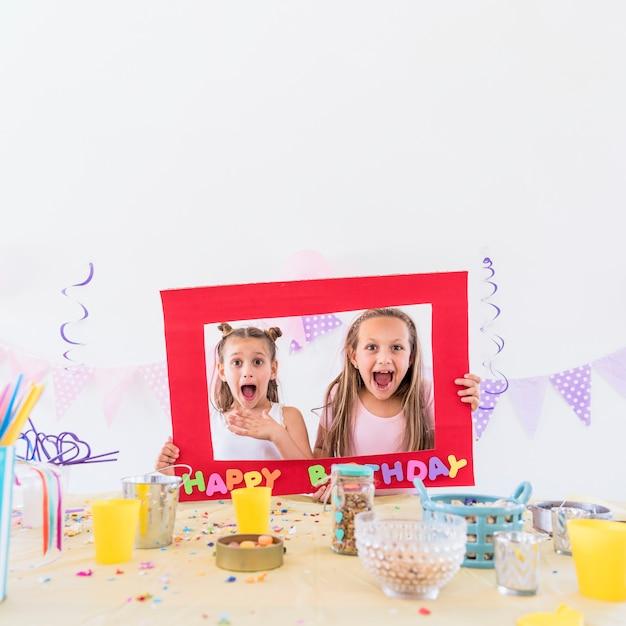 Una vista frontale di due ragazze che tengono la cornice del testo di compleanno dietro il tavolo alla festa Foto Gratuite