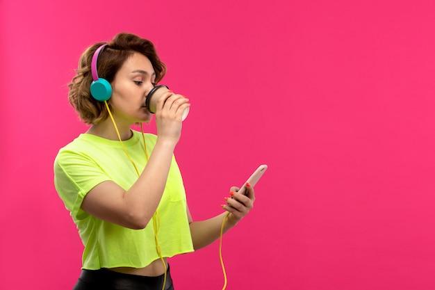 Una vista frontale giovane donna attraente in camicia color acido pantaloni neri in cuffie blu hearignign musica usando il suo telefono a bere caffè sullo sfondo rosa giovani donne giovani Foto Gratuite