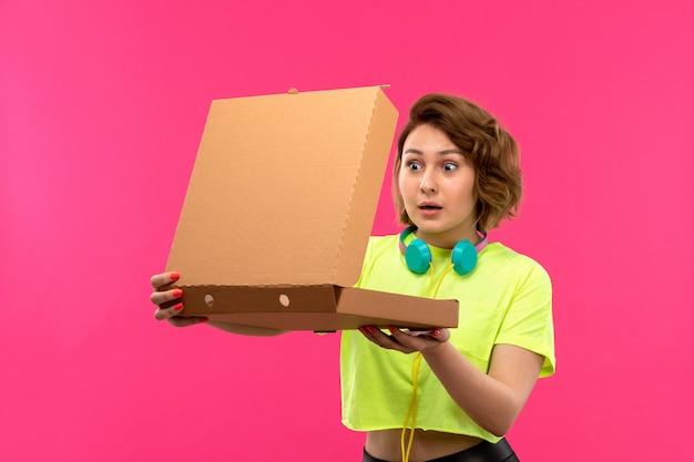 Una vista frontale giovane donna attraente in camicia di colore acido pantaloni neri auricolari blu apertura scatola marrone sullo sfondo rosa giovane musica femminile Foto Gratuite
