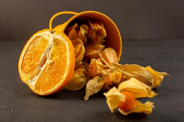 Una vista frontale ha affettato le arance insieme ai frutti rotondi arancio sbucciati sparsi sul gray Foto Gratuite
