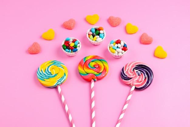Una vista frontale lecca-lecca colorate su bastoncini di paglia dolce rosa-bianco insieme a marmellate a forma di cuore e caramelle multicolori su rosa Foto Gratuite