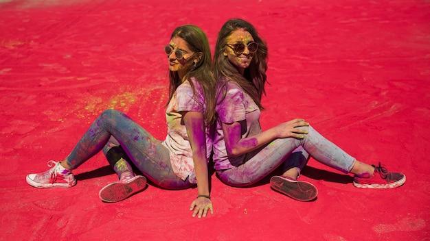 Una vista laterale di due giovane donna che si siede di nuovo al pasticcio con colore di holi Foto Gratuite