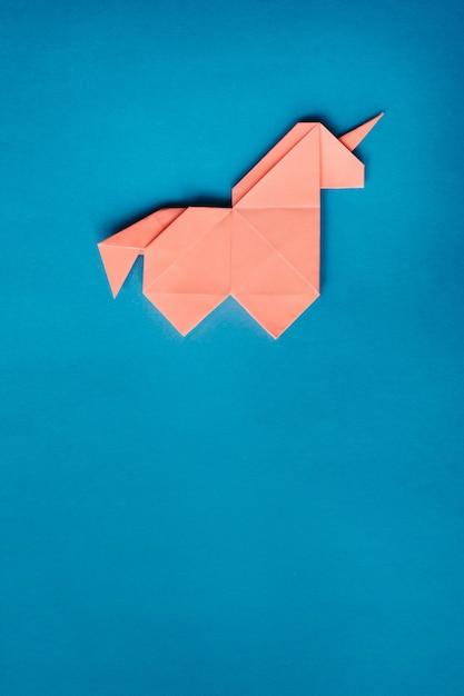 Unicorno rosa di origami su fondo blu Foto Premium