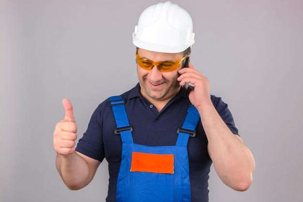 Uniforme da costruzione e casco di sicurezza d'uso dell'uomo del costruttore che parlano sul telefono cellulare felice e che sorride mostrando i pollici su sopra la parete bianca isolata Foto Gratuite