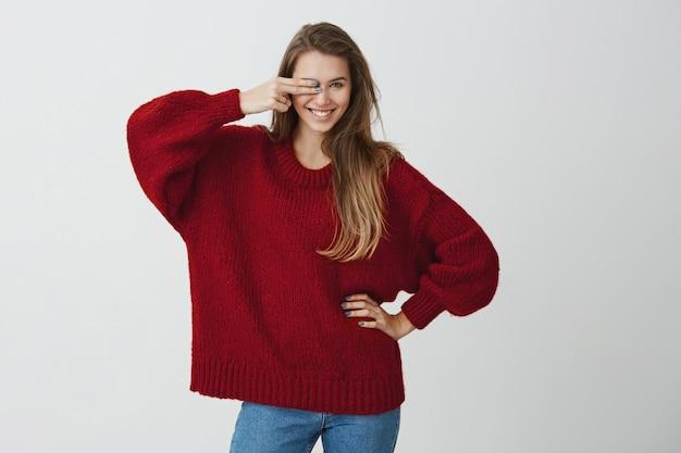 Uno sguardo e non hai possibilità. ragazza emotiva di bell'aspetto in maglione sciolto rosso che copre l'occhio con il gesto della pistola, sorridendo ampiamente e flirtando, guardando sensualmente. Foto Gratuite