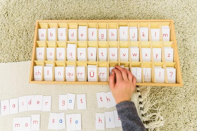 Uno studente di una scuola montessori che usa le carte con le lettere per comporre parole e frasi su una stuoia. Foto Premium