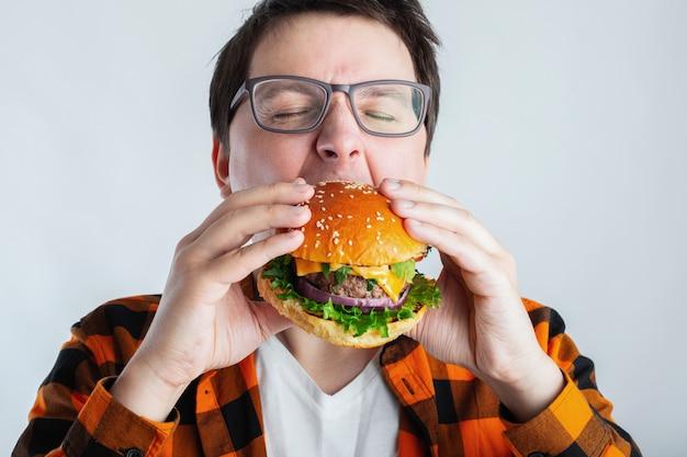 Uno studente molto affamato mangia il fast food. Foto Premium