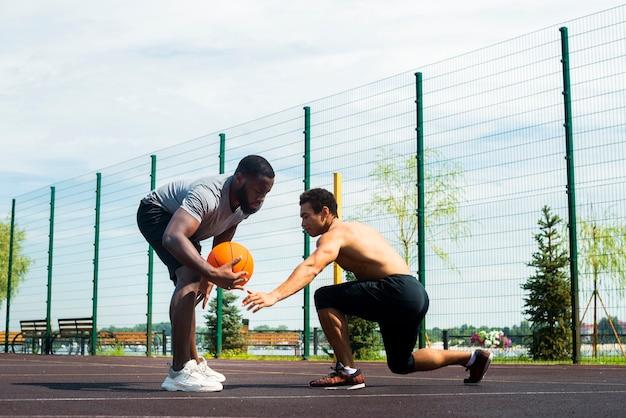 Uomini americani che giocano a pallacanestro urbano colpo lungo Foto Gratuite
