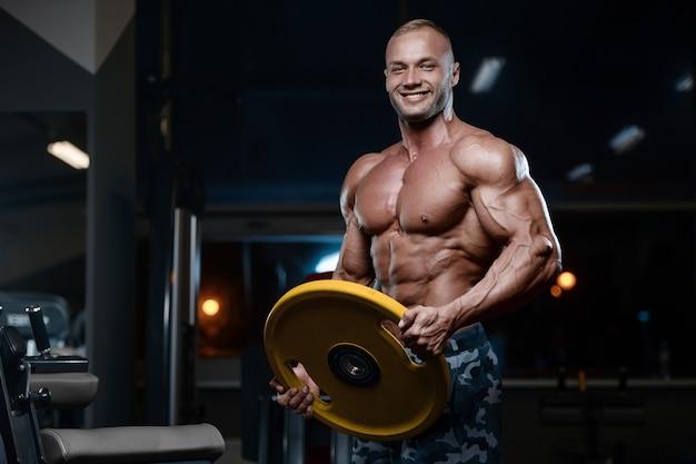 Uomini atletici brutali del culturista che pompano i muscoli con le teste di legno Foto Premium