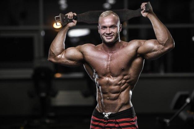 Uomini atletici del forte culturista bello che pompano i muscoli con le teste di legno Foto Premium